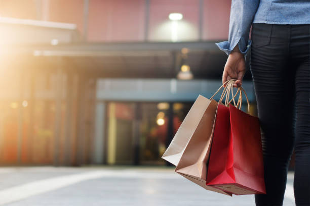 woman walking with shopping bags on shopping mall background stock photo