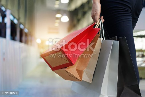 istock woman walking with shopping bags on shopping mall background. 672310532