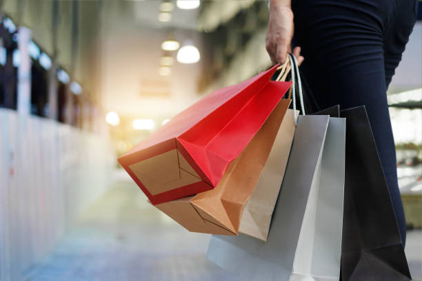 woman walking with shopping bags on shopping mall background. woman walking with shopping bags on shopping mall background. thailand mall stock pictures, royalty-free photos & images