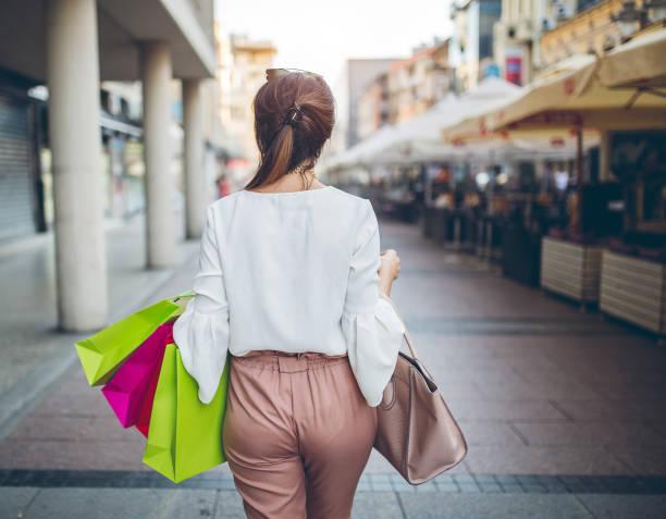 mujer caminando con bolsas de la compra. un disparo por la espalda. - buenos culos fotografías e imágenes de stock