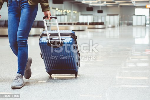 Woman in international airport walking with luggage. Close up of legs, unrecognizable person.