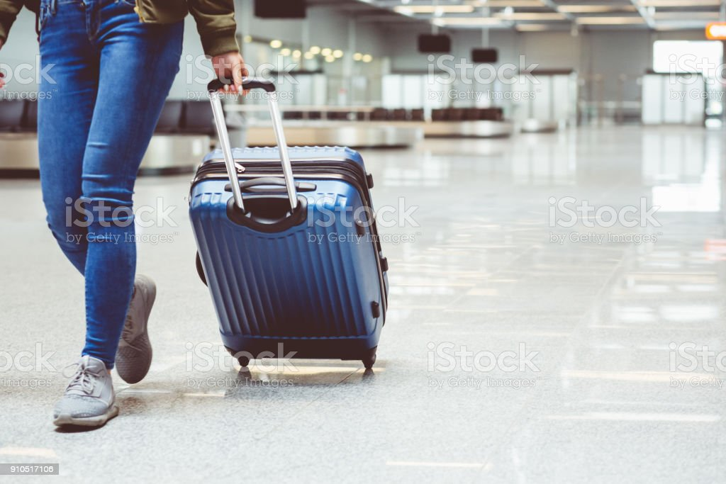 Woman walking with suitcase at airport terminal stock photo