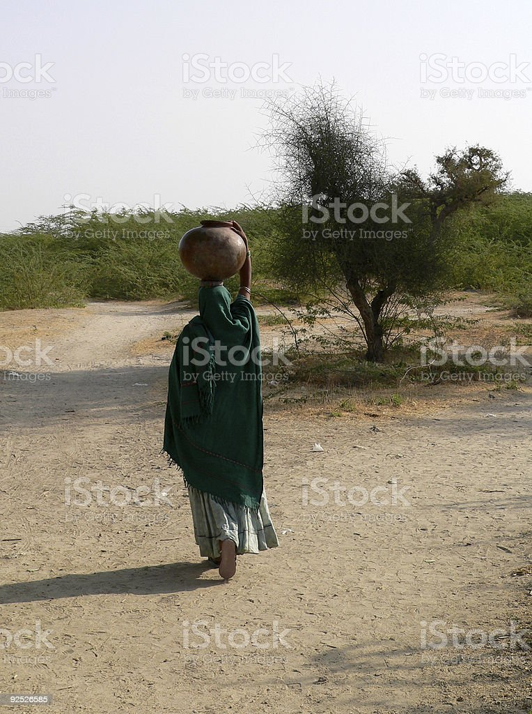 Woman walking with water jar in the desert, Rajasthan, India royalty-free stock photo