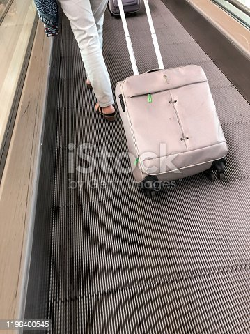 Woman walking with wheeled suitcase at Barcelona International airport, Spain