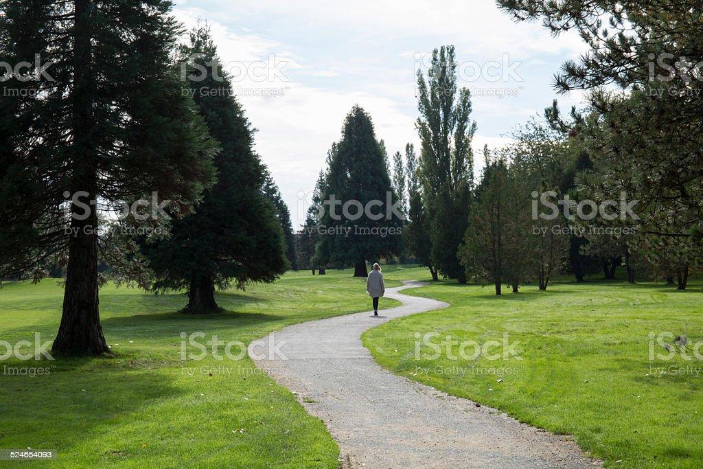 Woman walks along curving pathway through park stock photo