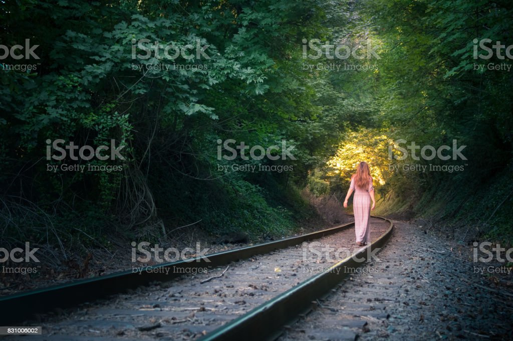 Woman walks along railroad tracks going towards the light stock photo