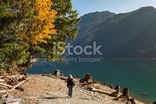 A woman walks along the shore of Baker Lake in North Cascades, Washington, USA