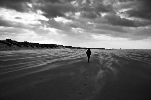 Woman walks along windswept Northsea beach