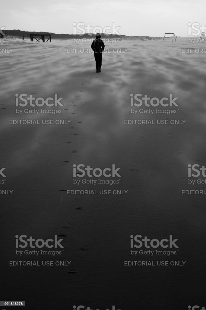 Woman walks along windswept Northsea beach stock photo