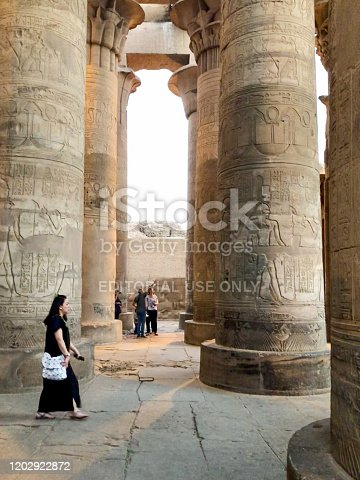 Kom Ombo, Egypt - 21 Okt, 2018: Woman walks between the large hieroglyph colums of the Kom Ombo temple