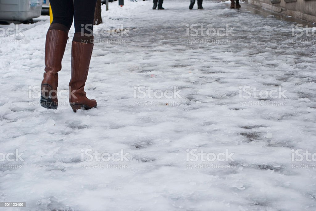 Woman walks on icy street stock photo