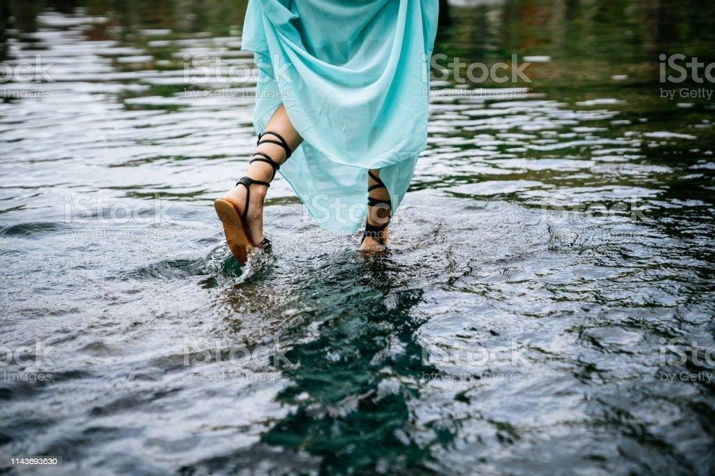 Woman in blue dress walks on water in Tirtagangga water palace