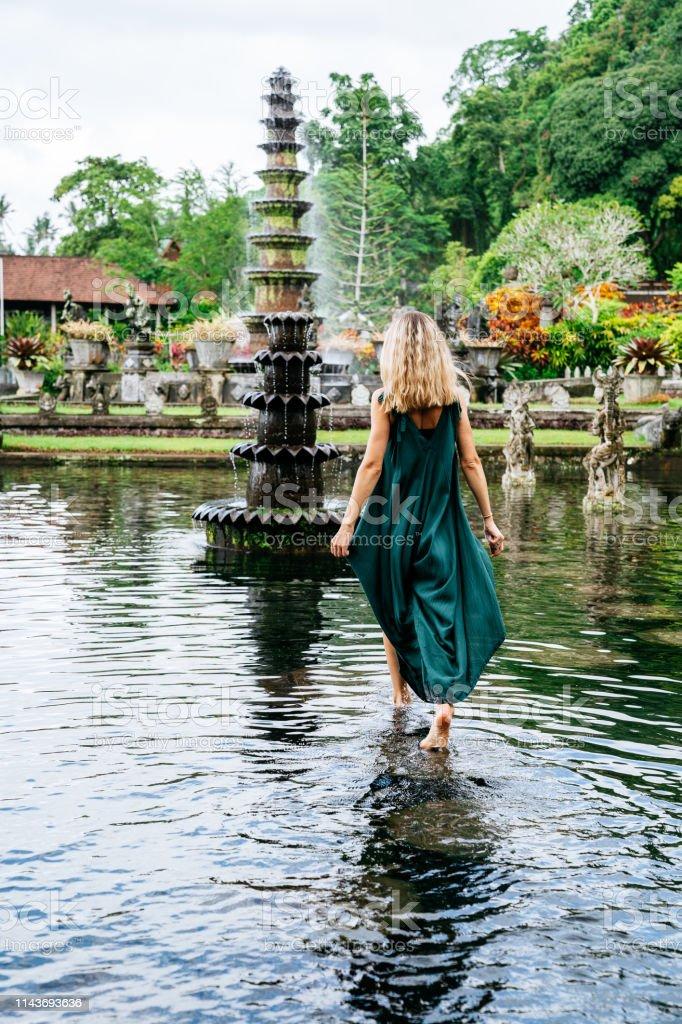 Woman in green dress walks on water in Tirtagangga water palace