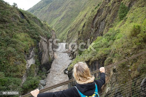 903015102 istock photo Woman walks over bridge spanning river gorge 961850004