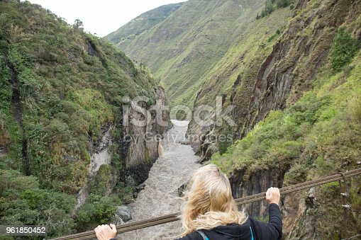 903015102 istock photo Woman walks over bridge spanning river gorge 961850452