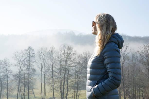 霧の中に起伏のある草原を歩く女性 - ダウンジャケット ストックフォトと画像