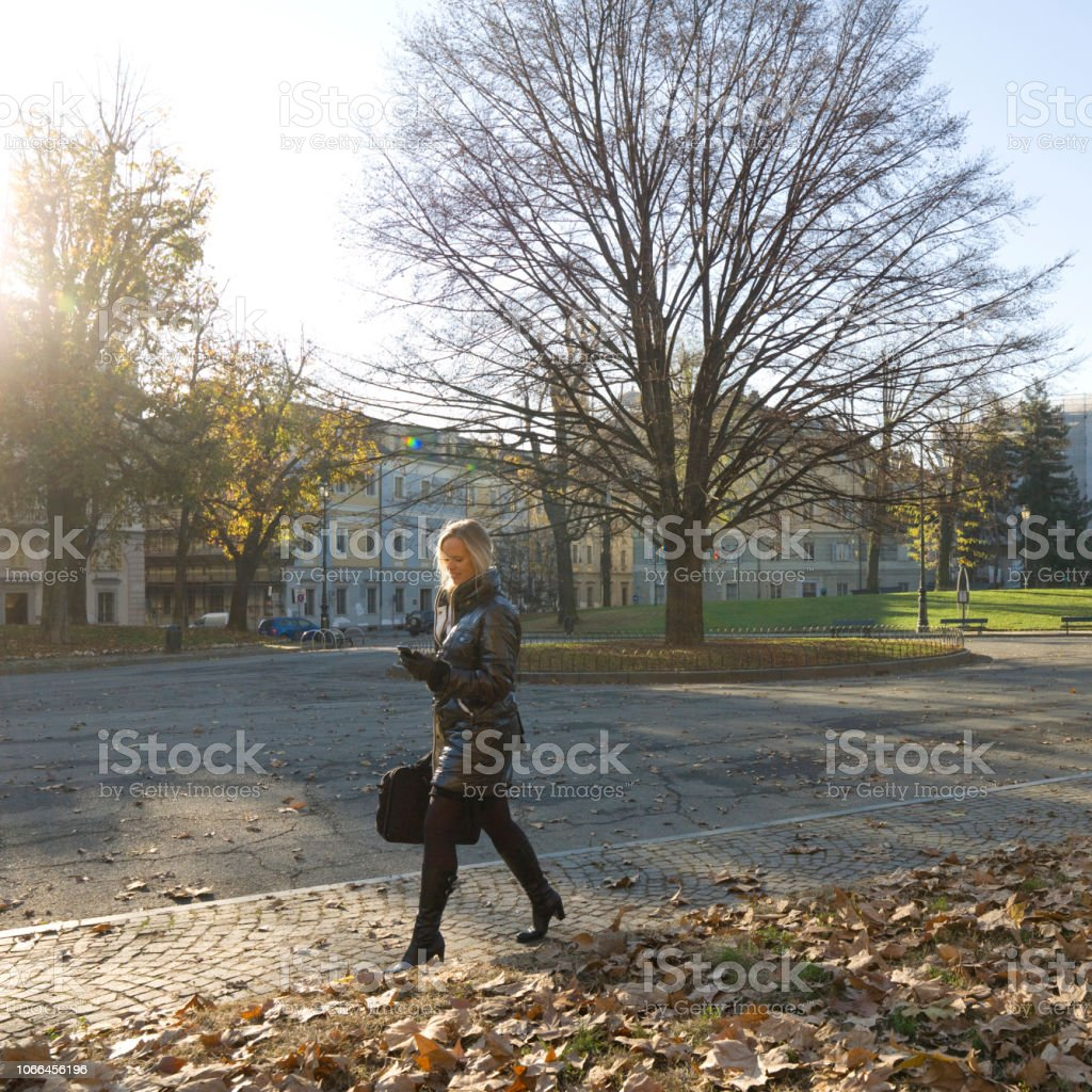 The sun is rising over the buildings behind her