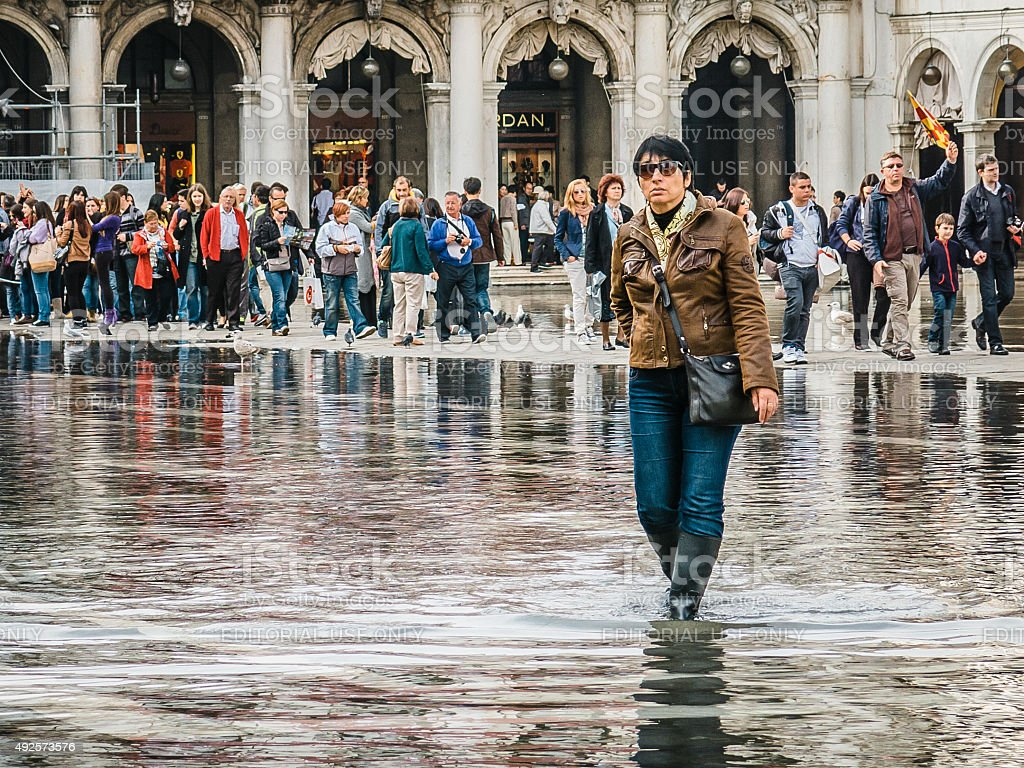 Woman walks through the acqua alta flood waters, St Marks. stock photo