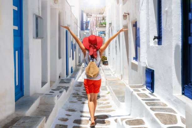 Woman walks through the white and blue streets of the Cyclades islands of Greece stock photo