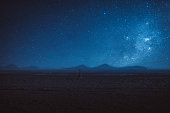 Woman stargazing at Atacama desert in Chile near the mountains at night