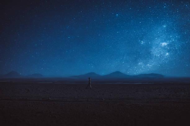 Woman walks under the million stars and Milky Way in Atacama desert stock photo