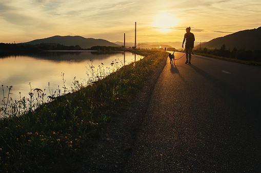 Woman walks with dog in sunset time