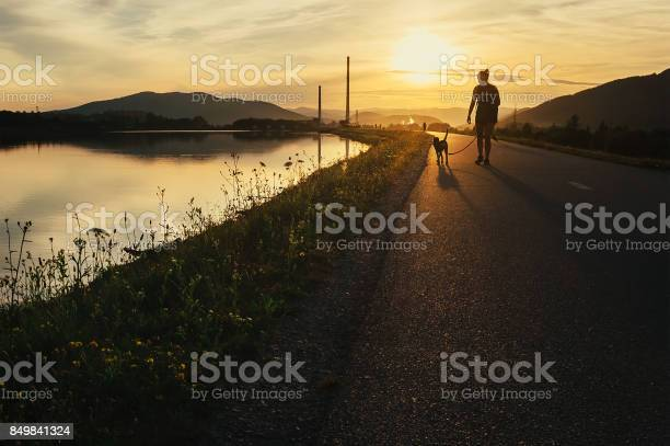Woman walks with dog in sunset time picture id849841324?b=1&k=6&m=849841324&s=612x612&h=cn76uupachjm zzck4ycfp3fqxampo3bi hwpdi3gcm=