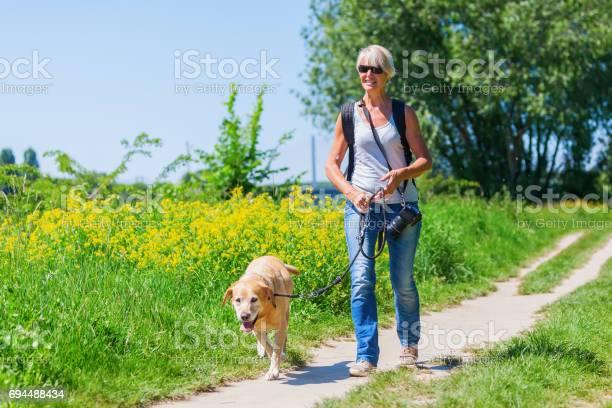 Woman walks with labrador retriever outdoors picture id694488434?b=1&k=6&m=694488434&s=612x612&h=sdfrircck6yceuzgd9mjhnsettuiosohpbkeqphnyua=