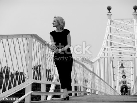 woman leaning on rail of bridge overlooking the railroad in Springfield Missouri