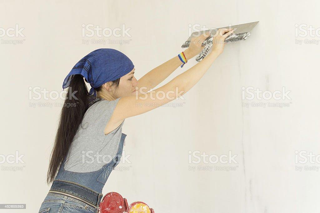 Woman wallpapering a wall royalty-free stock photo