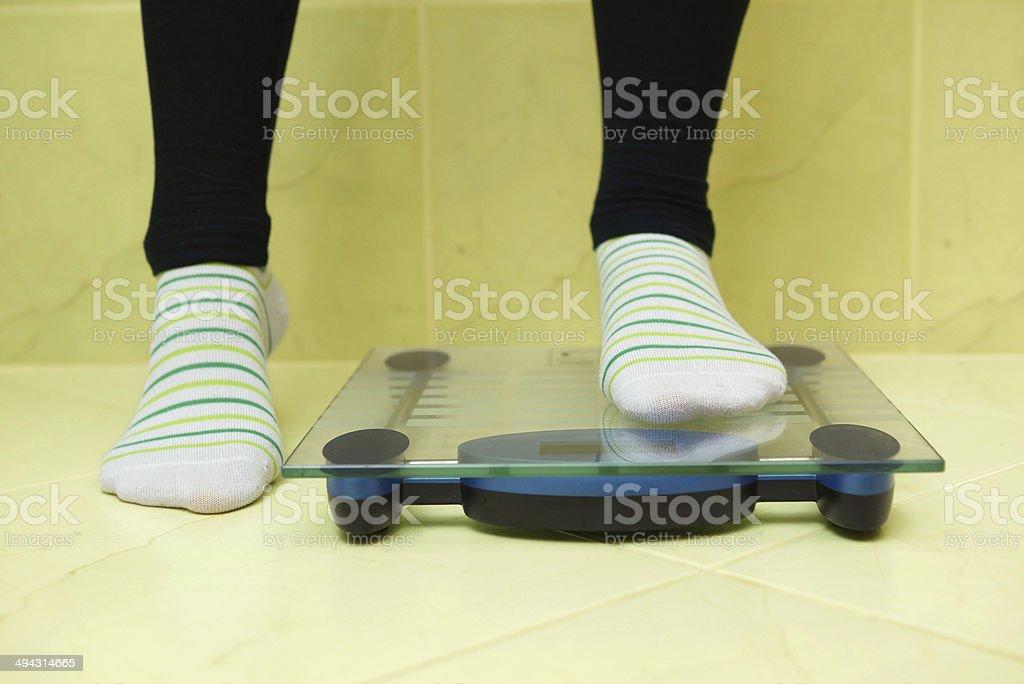 Mujer desea pesar y está en la balanza, - foto de stock