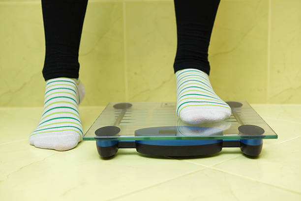 woman wants to weigh and stands on the scales stock photo