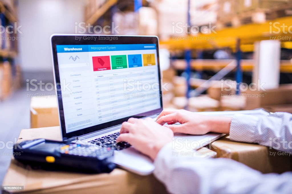 Woman warehouse worker or supervisor with laptop stock photo