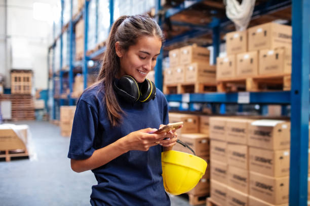 Woman warehouse worker using mobile phone stock photo