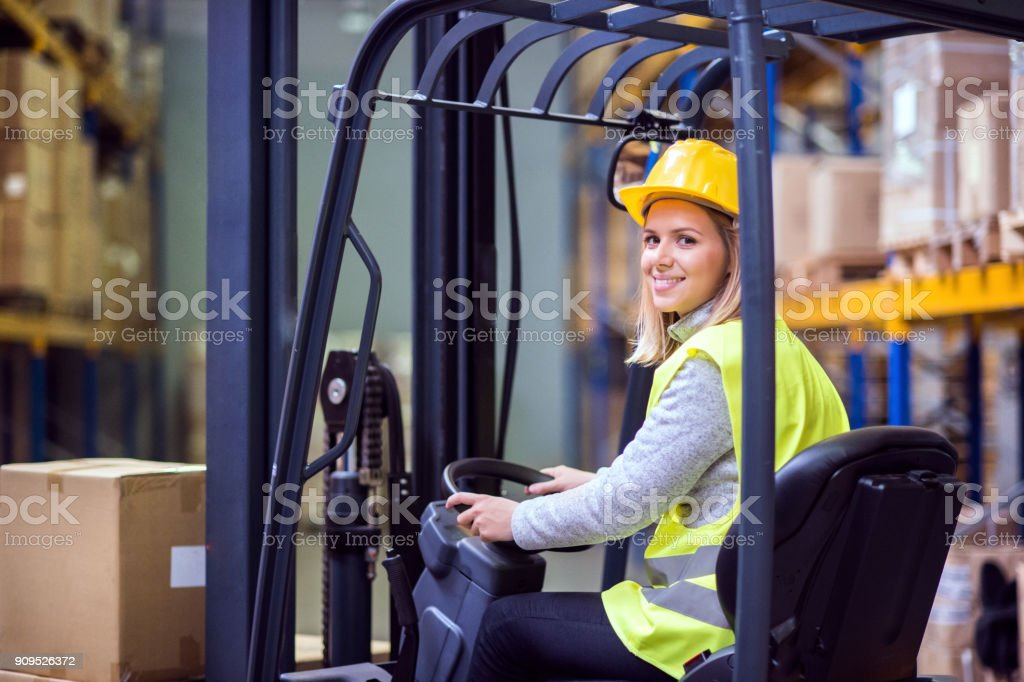 Woman warehouse worker with forklift. stock photo