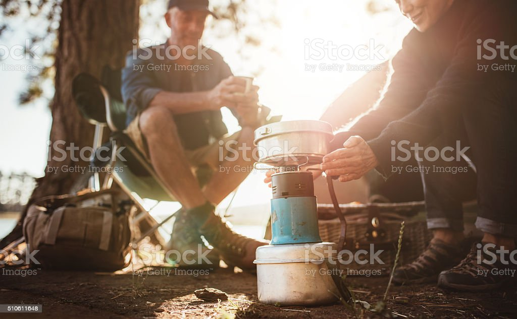 Woman warming hands on stove at campsite stock photo