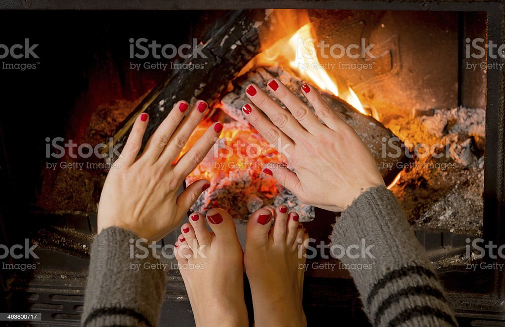 woman warming her hands ands feet stock photo