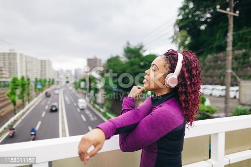 A woman is warming up while listening to music before running on a cloudy bad weather day.