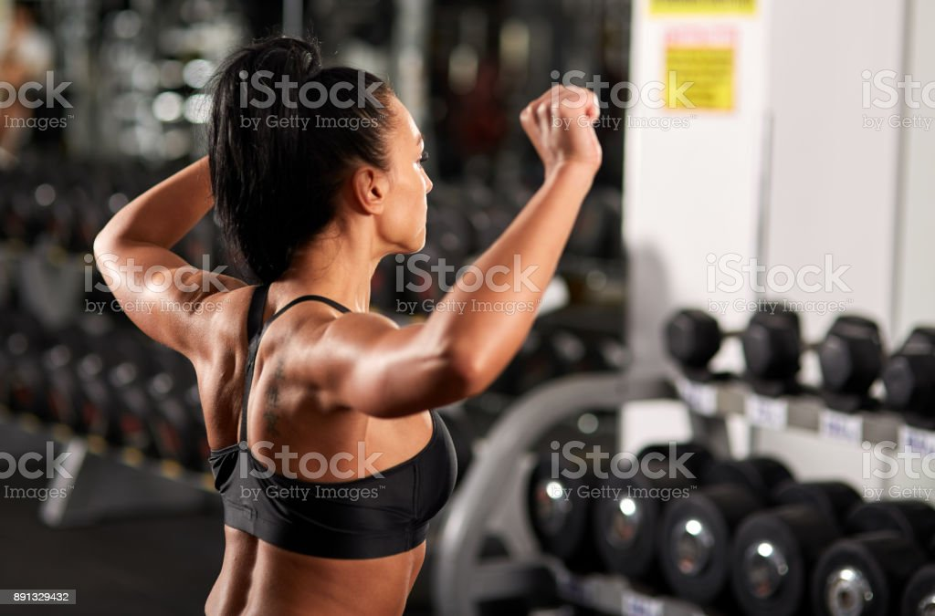 Woman warming up for shoulder workout stock photo