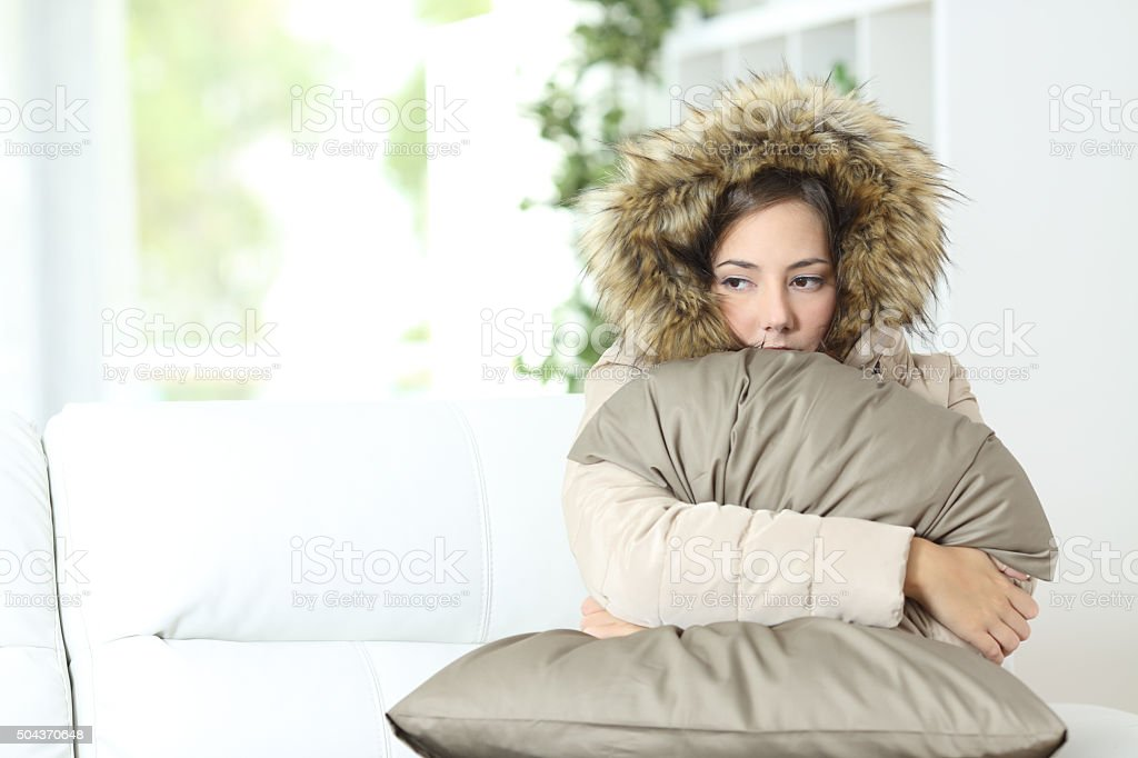 Woman warmly clothed in a cold home stock photo