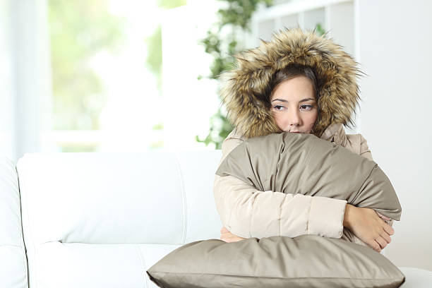 woman warmly clothed in a cold home - warm house stock photos and pictures