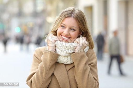 1051172208 istock photo Woman warmly clothed looking a side in winter in the street 1044204868