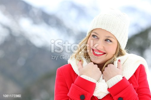 Happy woman warmly clothed in red looking at side in winter in the mountain