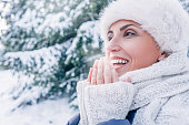 istock Woman warms her fingers with breathing 870960804
