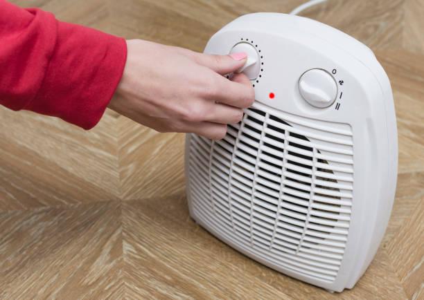 kvinna värmer händerna frysta nära en elektrisk fläkt värmare hemma. selektivt fokus. - kvinna ventilationssystem bildbanksfoton och bilder