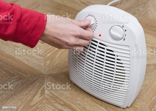 Photo of Woman warms her frozen hands near an electric fan heater at home. Selective focus.