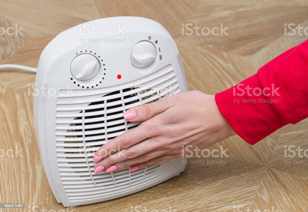 Woman warms her frozen hands near an electric fan heater at home. Selective focus. stock photo