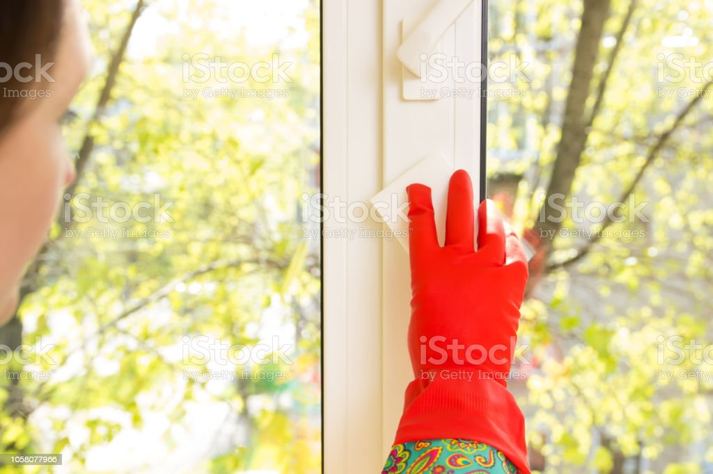 woman washes a window in the house. window cleaning. melamine sponge...