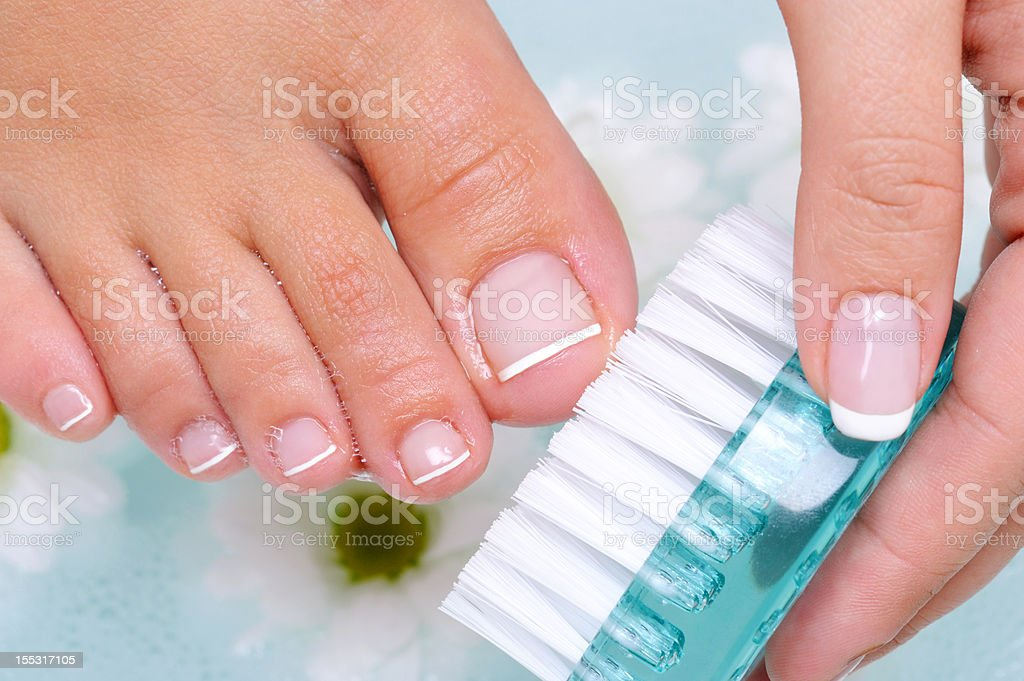 woman washes and cleans the toenails royalty-free stock photo
