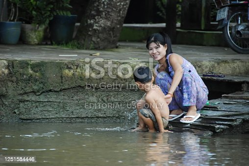 Can Tho, Vietnam - November 7th, 2008: Unidentified woman washes her child in The Mekong River in a countryside of Can Tho, Vietnam. The Mekong River plays significant role for dwellers of its delta.